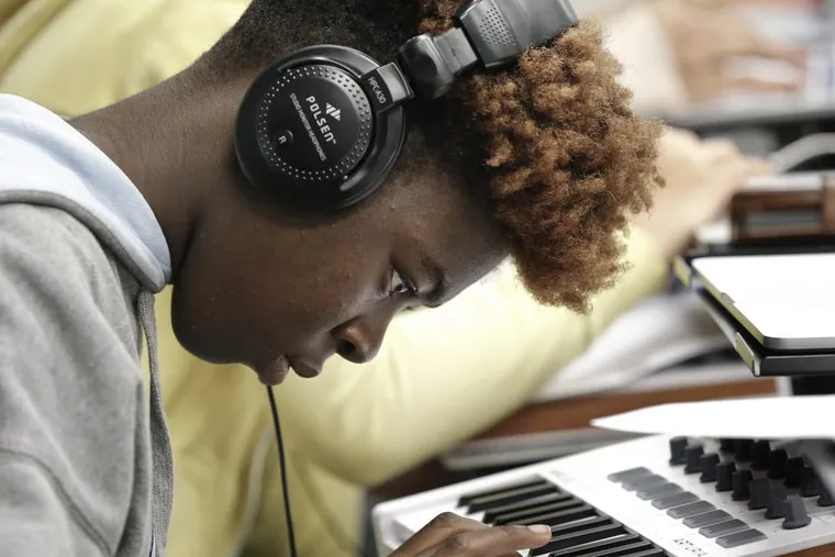 """LINC H.S. senior Teo O'Brien makes music during the """"Songwriting 101"""" class at the Philadelphia School District headquarters."""
