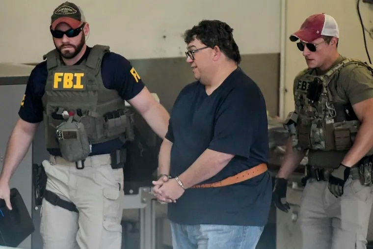 FBI agents escort businessman Fernando Scherrer-Caillet who was arrested in San Juan, Puerto Rico, Wednesday, July 10, 2019. Puerto Rico's former secretary of education and four other people including  Scherrer-Caillet have been arrested on charges of steering federal money to unqualified, politically connected contractors. The alleged fraud involves $15.5 million in federal funding between 2017 and 2019.  (AP Photo/Carlos Giusti)