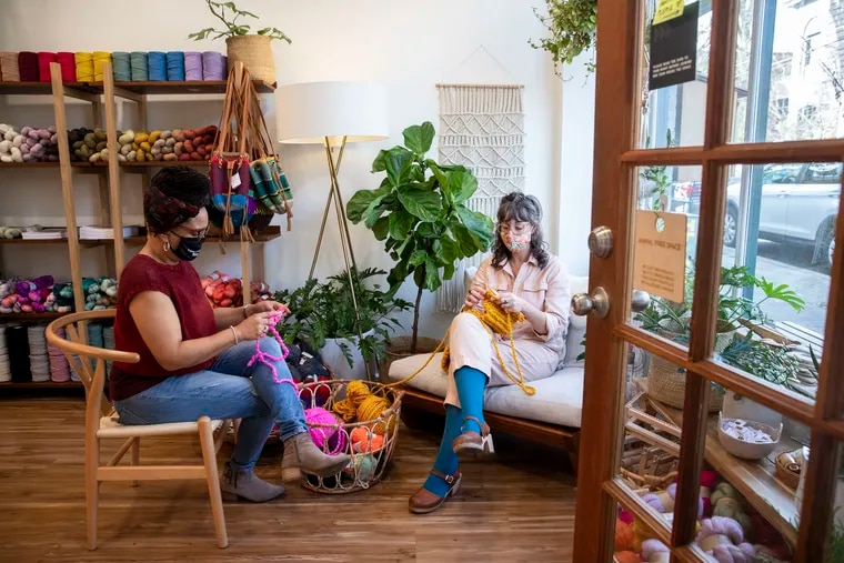 Yolanda Booker (left) and Liz Sytsma demonstrate how to knit a basic winter scarf at Sytsma's Mt. Airy shop, Wild Hand.