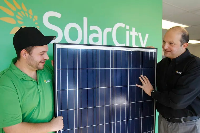 Leon Keshishian (right), SolarCity's regional vice president, and Russell Pierson with a solar panel. (AKIRA SUWA / File Photo)