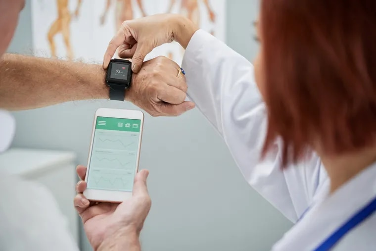 Doctor showing senior patient how to synchronize health app in smartphone and smartwatch.