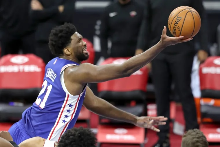 Joel Embiid, top, of the SIxers scores against Gabe Vincent of the Heat during the 3rd quarter of a NBA game at the Wells Fargo Center on Jan. 12, 2021.