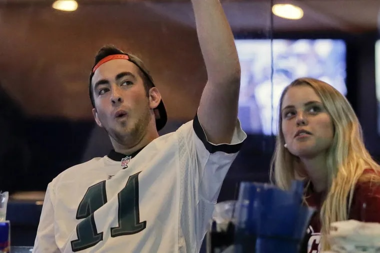 Keith McDonald of Millersville, Pa. and Tabitha Evans of Landisville, Pa. (formerly from Collegeville) cheer for an Eagles touchdown while watching the Dolphins-Eagles preseason game at Arooga's Grille House & Sports Bar in Lancaster.