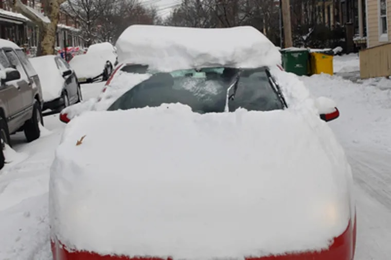 Barely bothering to clear the snow from his car, a driver is stopped at the traffic light on Collins Avenue at Haddon Avenue in Collingswood, Monday morning. (Tom Gralish / Staff Photographer)