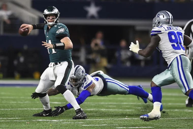 Eagles quarterback Carson Wentz throws a pass to Alshon Jeffery for a first down in the fourth quarter after evading Cowboys linebacker Damien Wilson on Sunday.