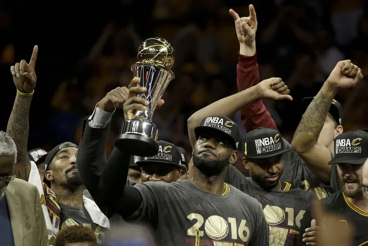 Cleveland Cavaliers forward LeBron James, center, celebrates with teammates after winning NBA championship.