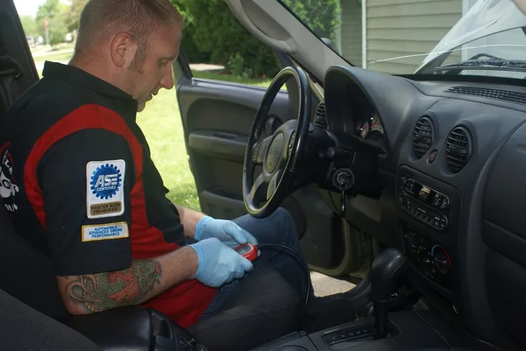 Otobots mechanic Peter Champlin works on a 2003 Jeep Liberty in the vehicle owner's driveway in Streamwood, Ill.