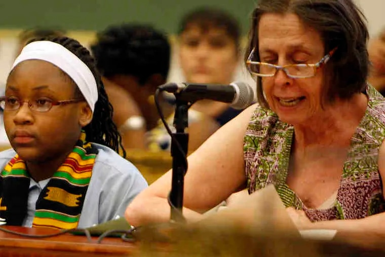 Dei'Vion Wescott, 11, joins Ann Guise, director of the Bright Lights Initiative, an educational- advocacy group, as she testifies during City Council hearing.