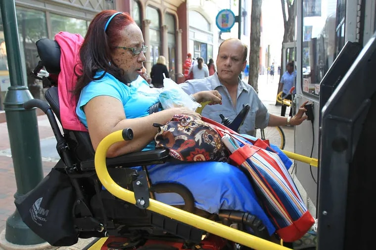 Carol Johnson , after doing some volunteer work, is helped into a paratransit vehicle by driver Manny Vasquez. Her travels may soon get easier as 45 more disabled-accessible taxis could be on city streets by year's end. Story, B2. CHARLES FOX / Staff Photographer
