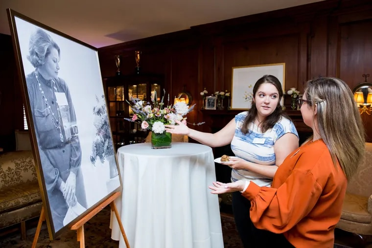 Two attendees of the Philadelphia Flower Show theme reveal look at a portrait of Princess Grace Kelly.