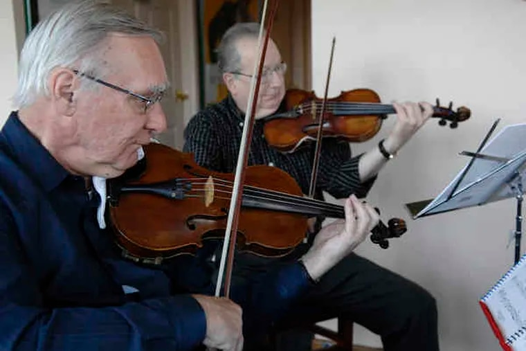 Tom Angell and Lutz Mueller, of Settlement Music School's Adult Chamber Players performed yesterday at the art show reception.