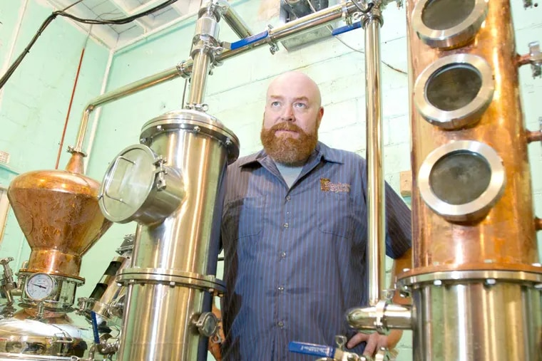 Dean Browne stands by his new still at Rowhouse Spirits  on Frankford Ave.   ( CHARLES FOX / Staff Photographer )
