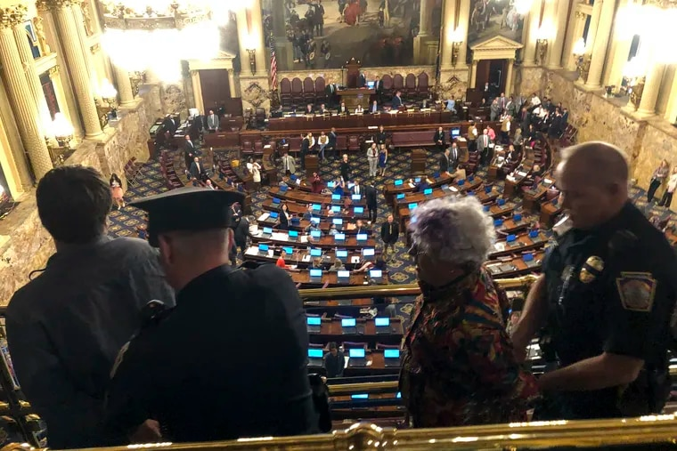 Demonstrators protesting a Pennsylvania law that doesn't limit how much in gifts state lawmakers may accept from people seeking to influence them are arrested and led out of the House of Representatives' chamber in the state Capitol in Harrisburg, Pa., Monday, May 6, 2019. (AP Photo/Marc Levy)