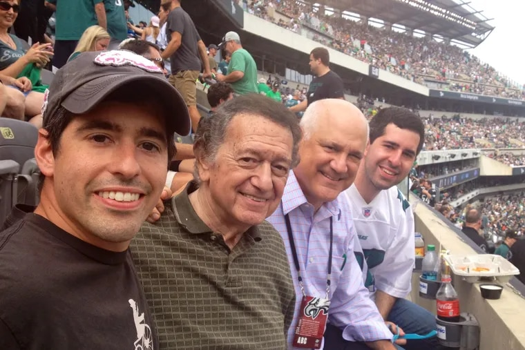 Physician Theodore Macnow (left) author of a new concussion study, joined grandfather Marvin Macnow, father and WIP radio host Glen Macnow, and brother Alex Macnow (also a physician) at an Eagles game in 2019.