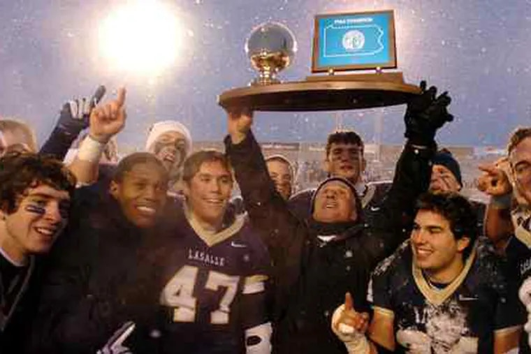"""Head coach Drew Gordon holds aloft the PIAA Class AAAA trophy as the Explorers shout, """"We're No. 1."""" La Salle's defense held State College to just 124 yards in the 24-7 victory in Hershey, Pa."""