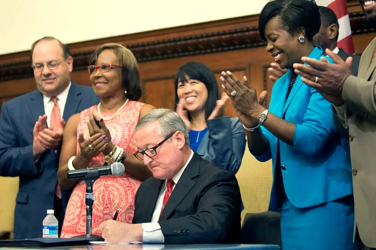 City Council members applaud as Mayor Jim Kenney signs the soda-tax bill at City Hall in a 2016 ceremony.