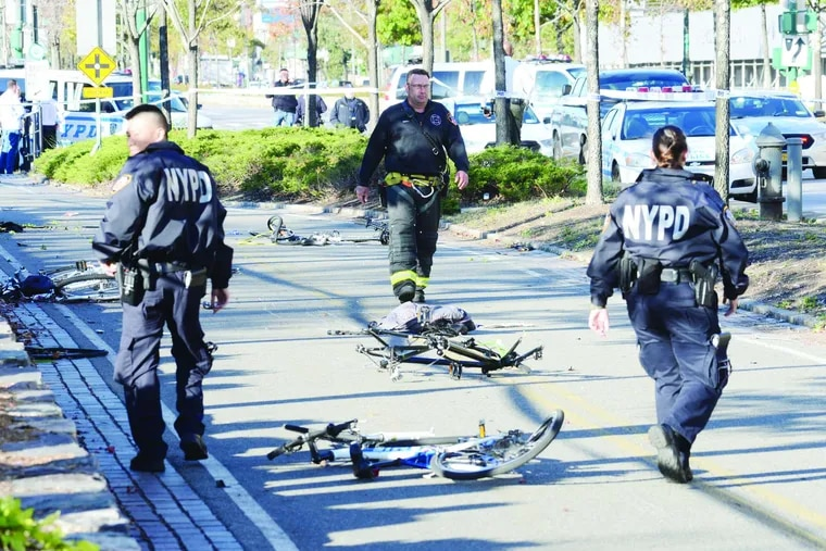 Police walk past mangled bikes after the driver emerged from a crashed rental truck after plowing down bike riders and pedestrianson a busy Lower Manhattan bike path.
