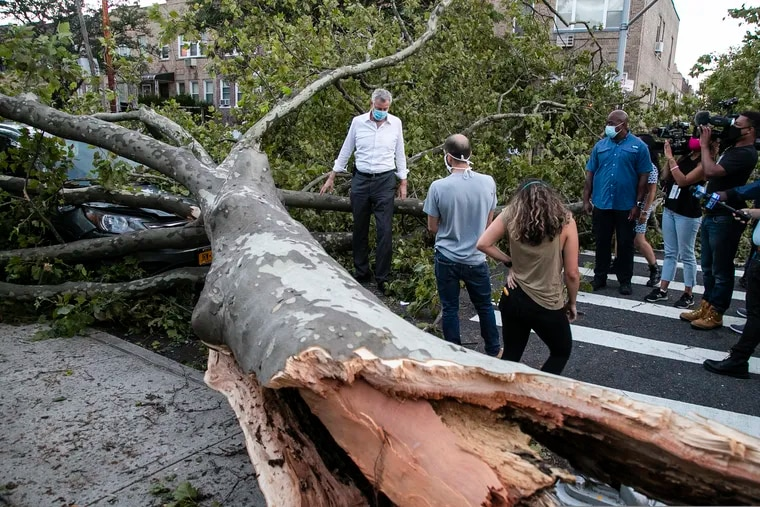 New York City Mayor Bill de Blasio (middle) talked with residents about damage from Tropical Storm Isaias on Tuesday in the Queens borough of the city.
