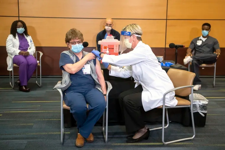 Charmaine Pykosh, an acute care nurse practitioner, receives Pfizer's COVID-19 vaccine from Tami Minnier, chief quality officer, at UPMC Children's Hospital of Pittsburgh, Monday, Dec. 14, 2020. (Alexandra Wimley/Post-Gazette)