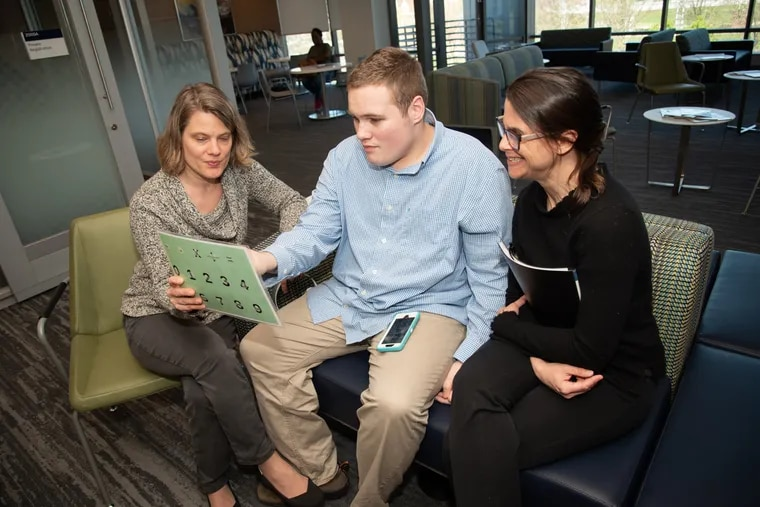 A patient and his mother (left) work with Dr. Wendy J. Ross, director of Jefferson Health's Center for Autism and Neurodiversity.