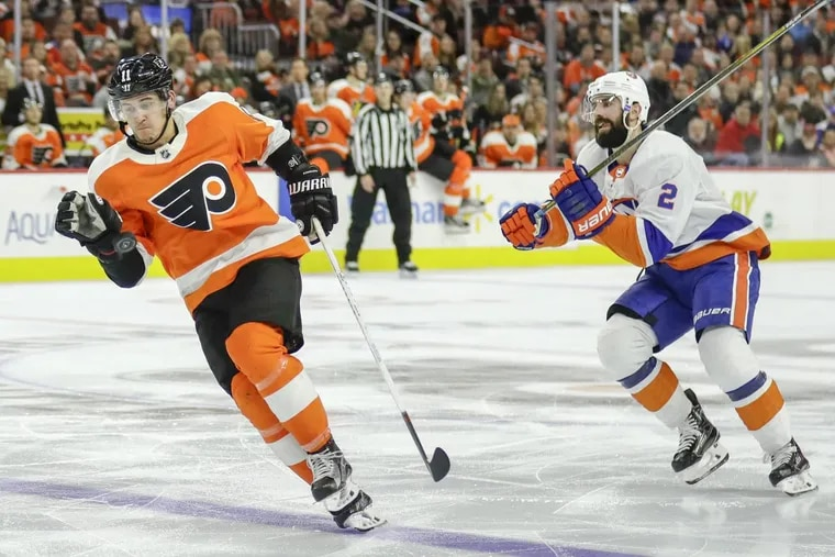The Philadelphia Flyers' Travis Konecny, left, plays the puck during a third-period breakaway past New York Islanders defenseman Nick Leddy at the Wells Fargo Center in Philadelphia on Friday, Nov. 24, 2017. The Isles won, 5-4, in overtime.