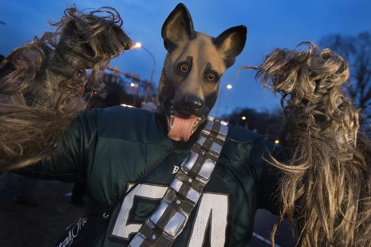 Eagles fan Michael Rahn, from West Chester, Pa., cheers while wearing his dog mask with a Chewbacca costume, hours before the start of the Eagles Super Bowl Champions parade on Broad St. in South Philadelphia. Thursday, February 8, 2018. JOSE F. MORENO / Staff Photographer