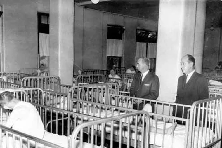 Adult patients at the Pennhurst State School and hospital at Slpring City, near Pottstown, Pa. spend their days and nights in cribs in the ward where they are destined to spend the rest of their lives. The school superintendent, Dr. Leopold A. Potkonski, left, and State Rep. Edwin G. Holl, chairman of the Montgomery County delegation, tour the ward Nov. 16, 1965. The asylum did not close until 1987.