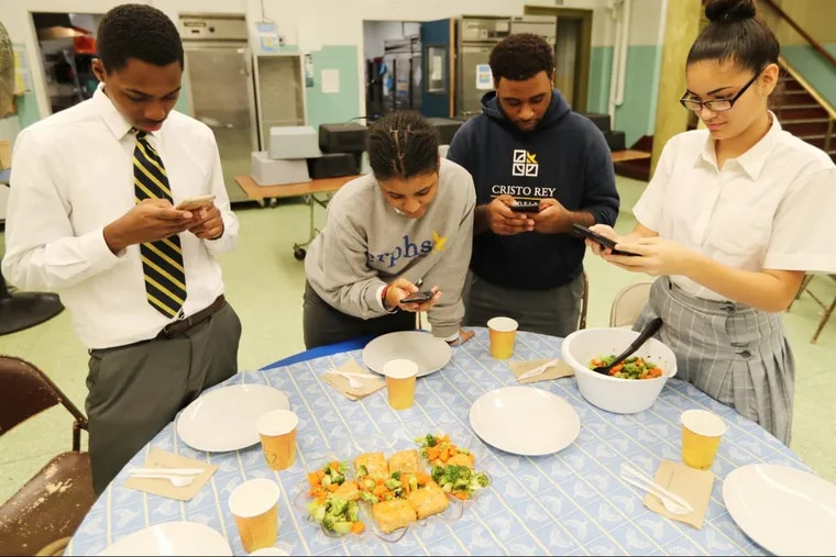 (L-R) Dashaun Dunmeyer, Essence Battle, Malachi Campbell and Olivia Rivera take photos of their glazed salmon with steamed broccoli and carrots meal.