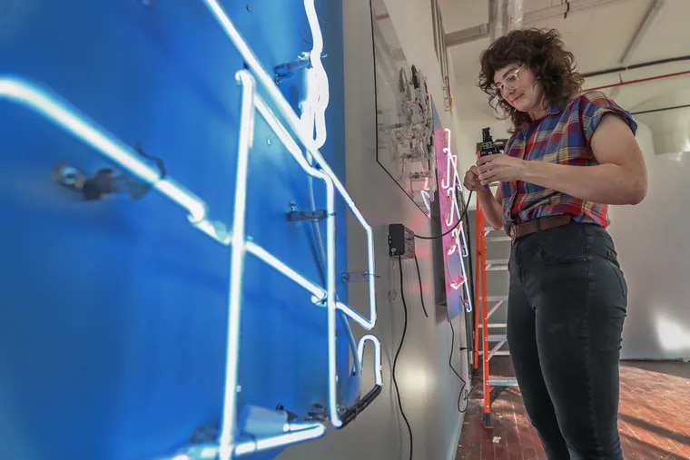 """Alissa Eberle, one of the region's only female glass benders works on connecting one of her neon art pieces, """"Dripping Rose"""" to electricty so it will glow, as she installs her show at Juggernaut Studios on Sunday September 29, 2019."""