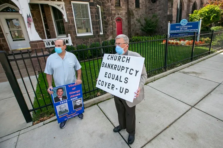 Arthur Baselice, Jr. and Robert Hoatson stand outside the  Cathedral of Immaculate Conception in Camden holding protest signs a day after the Camden diocese declared Chapter 11 bankruptcy. Arthur holds a board with an image of his son, who committed suicide after alleged sexual abuse by two priests.