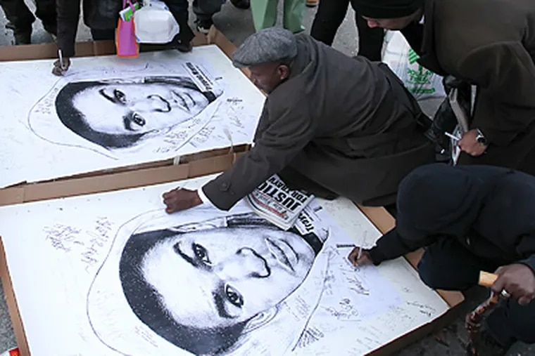 Philadelphians outraged by the Trayvon Martin case attended a candlelight vigil at LOVE Park on Monday, March 26, 2012. Here, participants signed artwork depicting Trayvon for a gallery show.   (Steven M. Falk / Staff Photographer)