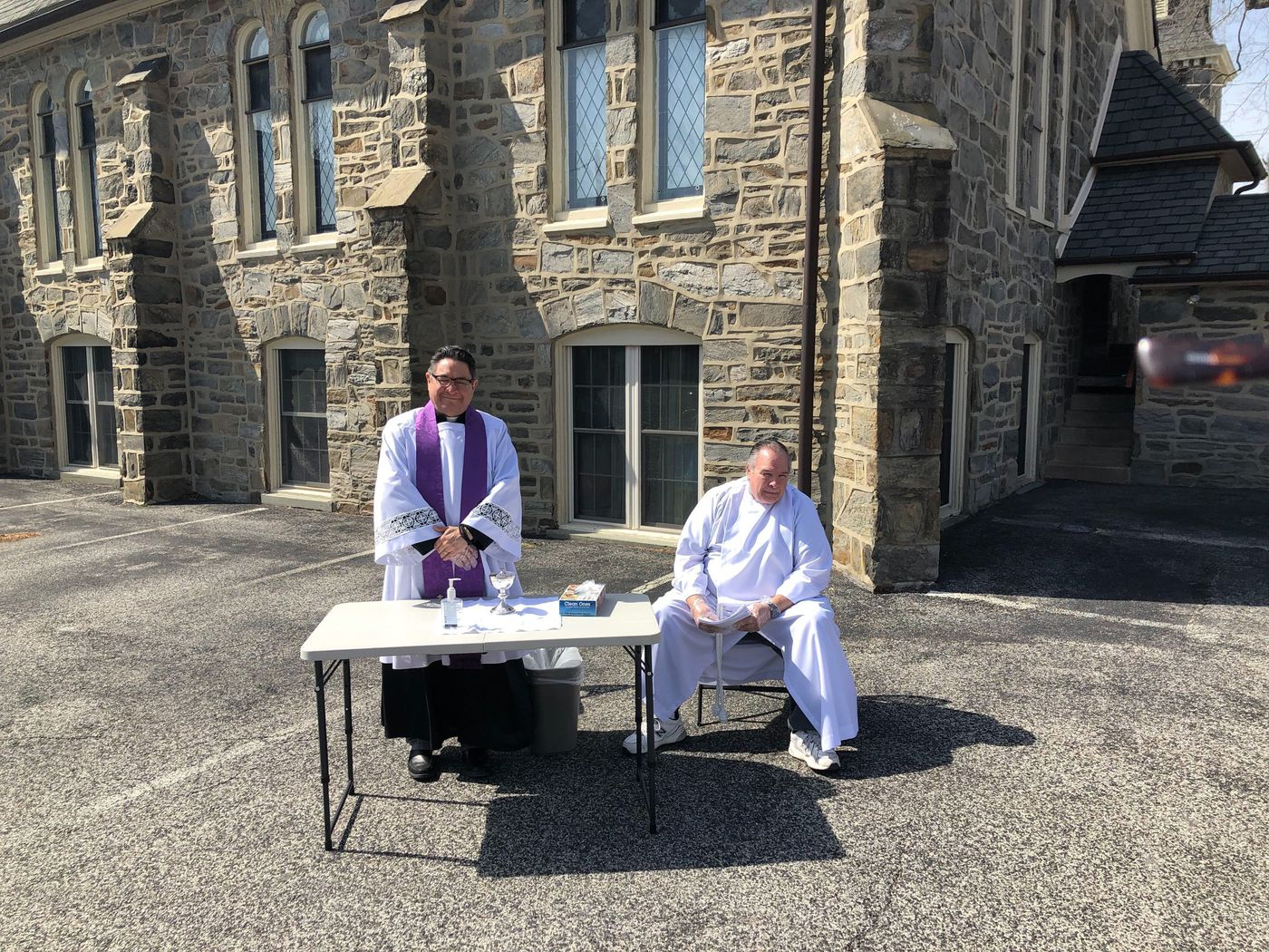 Rev. Ernie Galaz (left) of the Christ Episcopal Church in Media set up a drive-by and walk-by communion station.