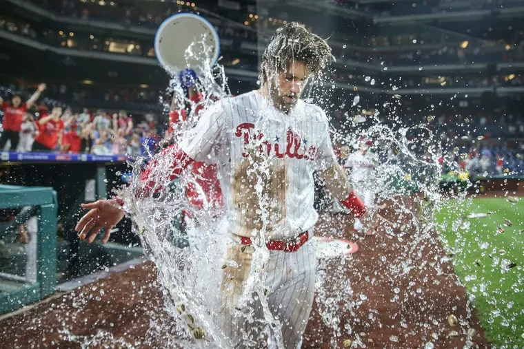 Phillies' Bryce Harper gets a dousing from teammate Jean Segura after his walk-off, two-run double against the Dodgers.