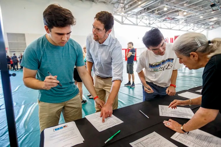Incoming Haverford College freshman Matthew Dodds, left, from Princeton, NJ, gets help from Haverford professor Zachary Oberfield, center, in filling out his voter registration form on the first day check-in for freshman at Haverford. The Delaware County election board on Monday unanimously voted to approve a request to put a polling place on the college campus.