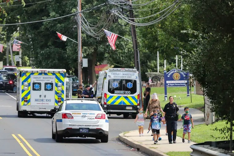 Kids are escorted by police away from the scene of what authorities described as a standoff with a man inside an apartment in the area of the Yardley Commons Condominium Complex on Wednesday. The Yardley police chief was shot in a standoff that ended hours later.