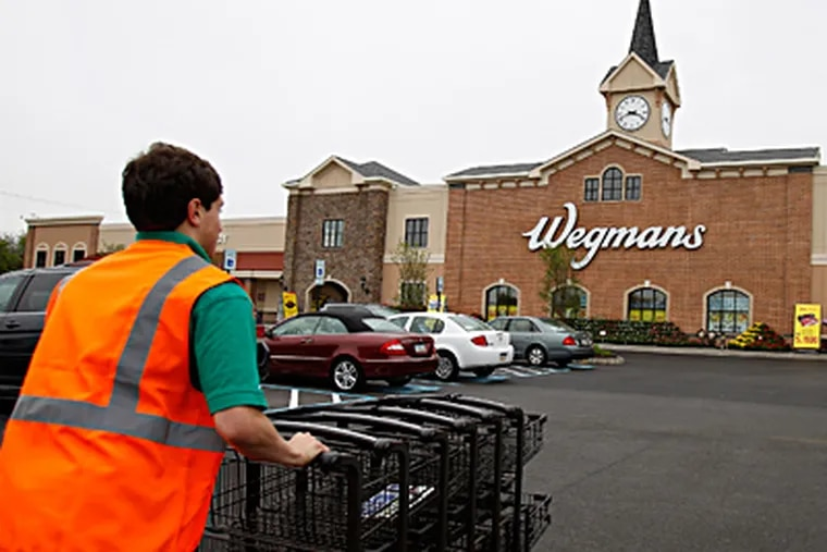 Employee Mark Phelan pushes shopping carts from the parking lot outside the new Wegmans store in King of Prussia. DAVID MAIALETTI / Staff Photographer