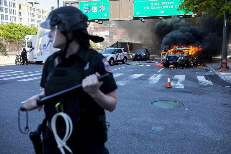 Philadelphia police make a wall to block protestors from approaching a burning Pennsylvania State Police car near the intersection of Broad and Vine Streets during May 30, 2020, protests over the death of George Floyd.