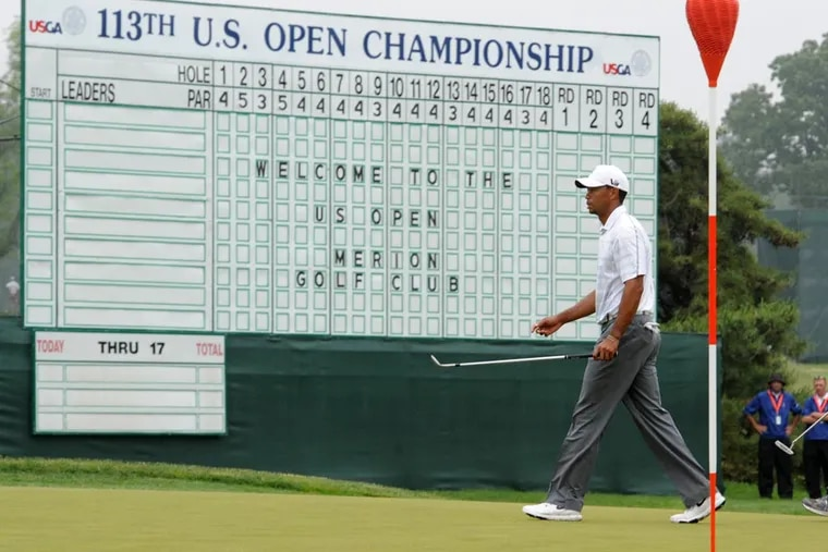 In this 2013 file photo, Tiger Woods walks past the leader board located at the 18th green at the Merion Golf Club in Ardmore during a practice round for the U.S. Open golf championship. On Tuesday, federal prosecutors in Philadelphia charged a U.S. Golf Association employee with stealing and reselling tickets to this and other Men's Open events.
