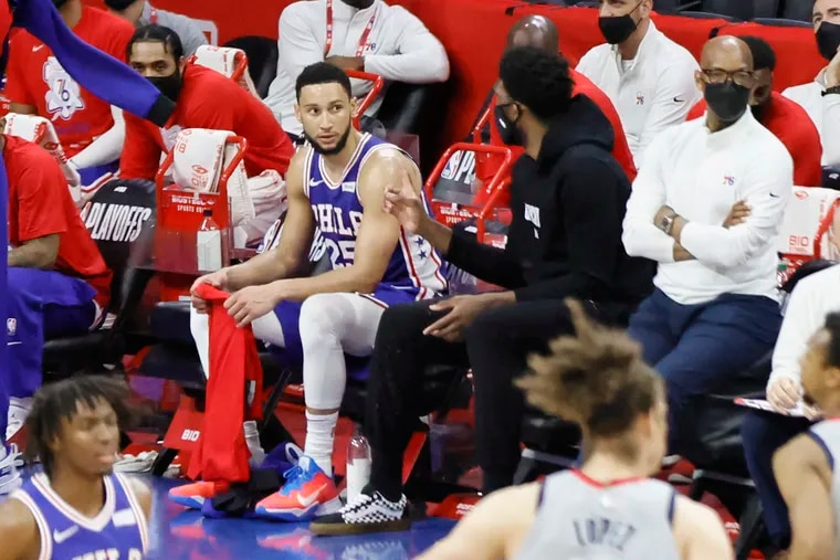 Ben Simmons (left) listens to Joel Embiid (in black) during a Sixers game last season.