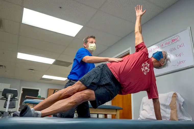 Physical therapist Travis Ross guides Steve Peterson through the side high plank windmill, an exercise to strengthen the lateral core muscles, at ChristianaCare Rehabilitation Services in Newark, Del.