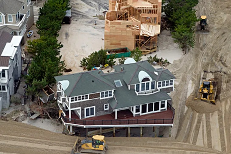 At Harvey Cedars, bulldozers went to work moving sand back into a dune formation Thursday. CLEM MURRAY / Staff Photographer
