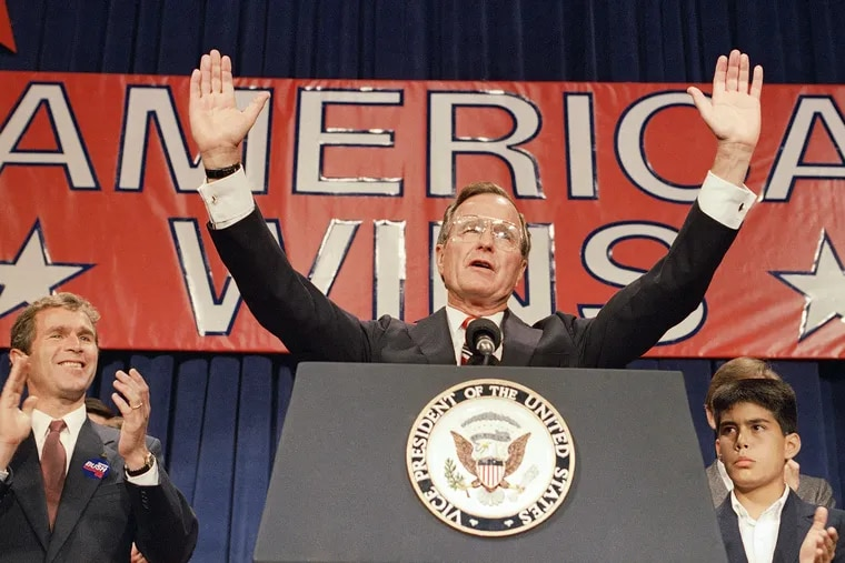 Then-President-elect George H. W. Bush holds his hands up to acknowledge the crowds applause, and ask them to allow him to continue his speech, during his victory rally with grandson, George P. Bush, right, and son George W. Bush, left, in Houston, Texas, on Election Night in November 1988.