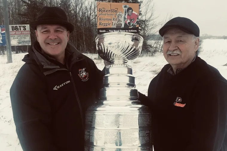 Former NHL player Jamie Leach (left) and his dad, Reggie, a one-time Flyers star, pose with the Stanley Cup in front of a billboard that salutes Reggie.