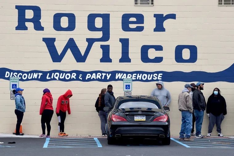 Patrons practice social distancing as they wait to be allowed to enter a liquor store in Pennsauken.