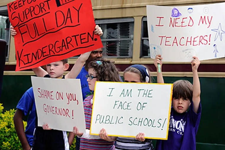 School children hold signs during a May 15 rally at the Trolley Car diner in Mount Airy protesting looming budget cuts that threaten public school services. (Ron Tarver / Staff Photographer)
