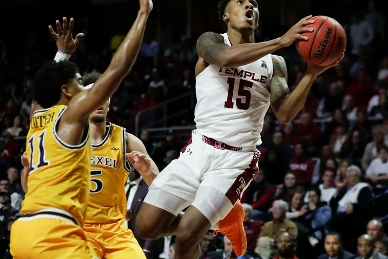 Temple guard Nate Pierre-Louis drives to the basket after getting fouled against Drexel guard Zach Walton (center) and guard Damian Dunn.