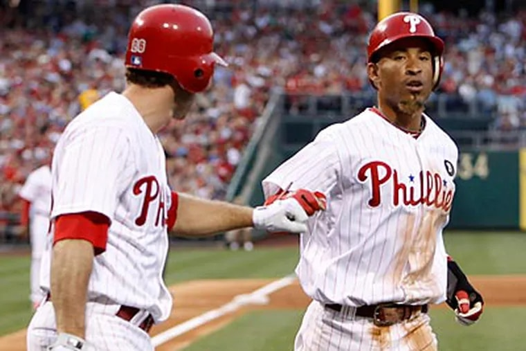 Wilson Valdez is congratulated by Chase Utley after scoring in the third inning. (Ron Cortes/Staff Photographer)