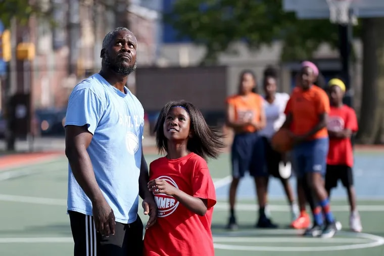 Shareef Baynes, left, and his daughter, Shariah Baynes, who is a 6th grader, watch her shot during a basketball camp at the Chew playground in Philadelphia.