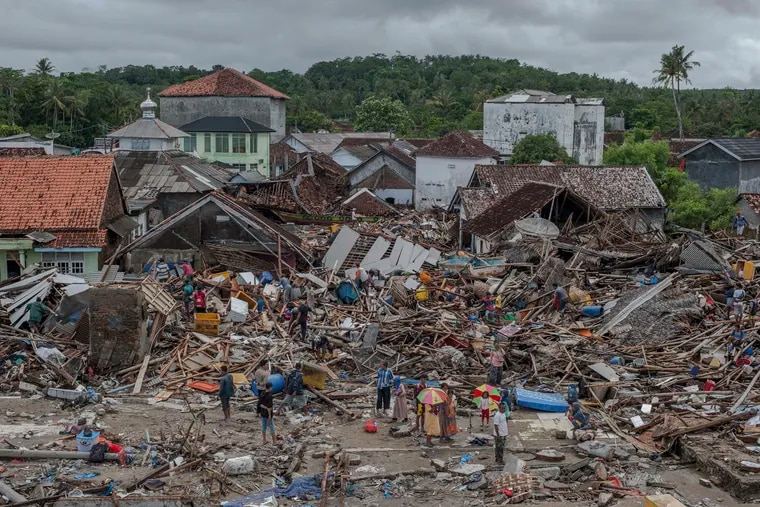 In this Monday, Dec. 24, 2018, photo, people inspect the damaged at a tsunami-ravaged village in Sumur, Indonesia. The tsunami that hit the coasts of Indonesian islands along the Sunda Strait was not big but it was destructive. The waves smashed onto beaches in the darkness Saturday night without warning, ripping houses and hotels from their foundations in seconds and sweeping terrified concertgoers into the sea. (AP Photo/Fauzy Chaniago)