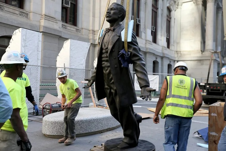 Workers installing a statue of Octavius V. Catto at City Hall in 2017.